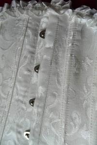 Gorset zapianany jest na metalowe zapinki. Widoczne szczegóły haftu.